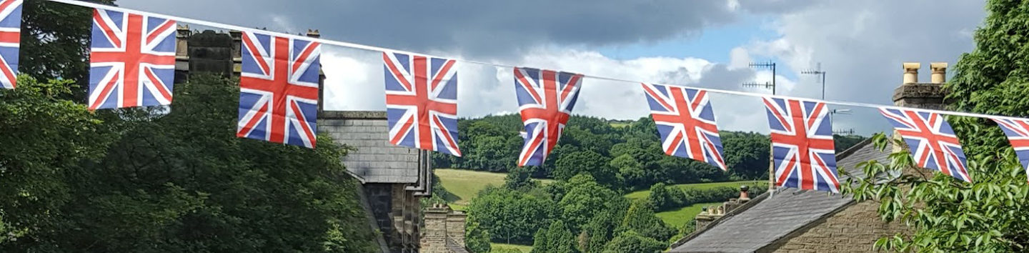 A Yorkshire hillside with british flag bunting suggesting the local benefits of Community Sponsorship